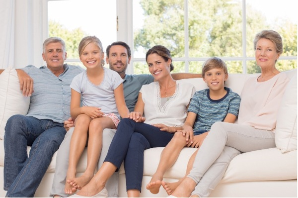 A family sitting on the couch together.