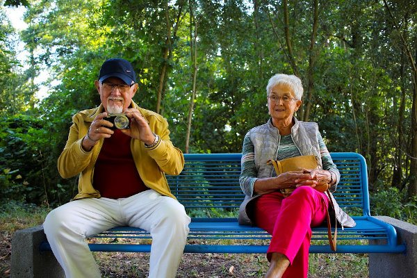 Two people sitting on a bench with a camera.