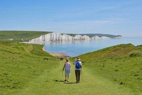Two people walking along a ridge.